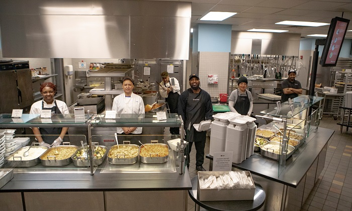 Five members of Campus Dining standing behind countertops with food on top