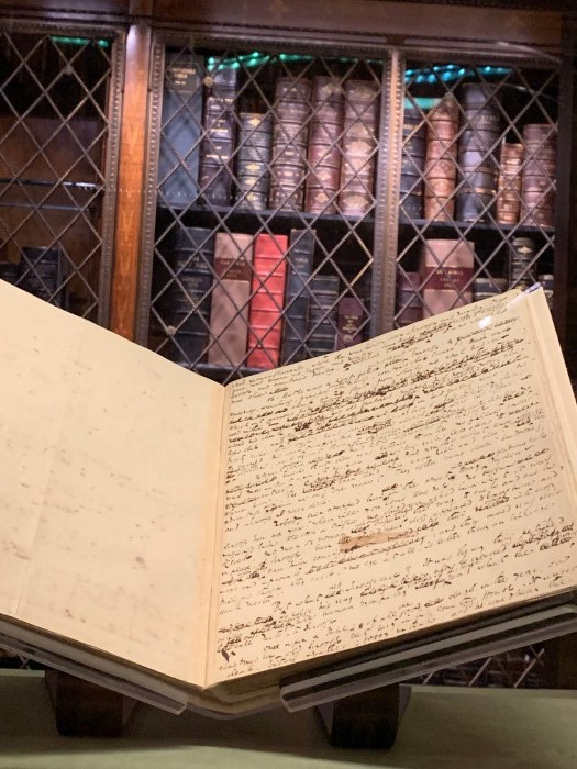 Open manuscript in Morgan Library with shelves of books in the background