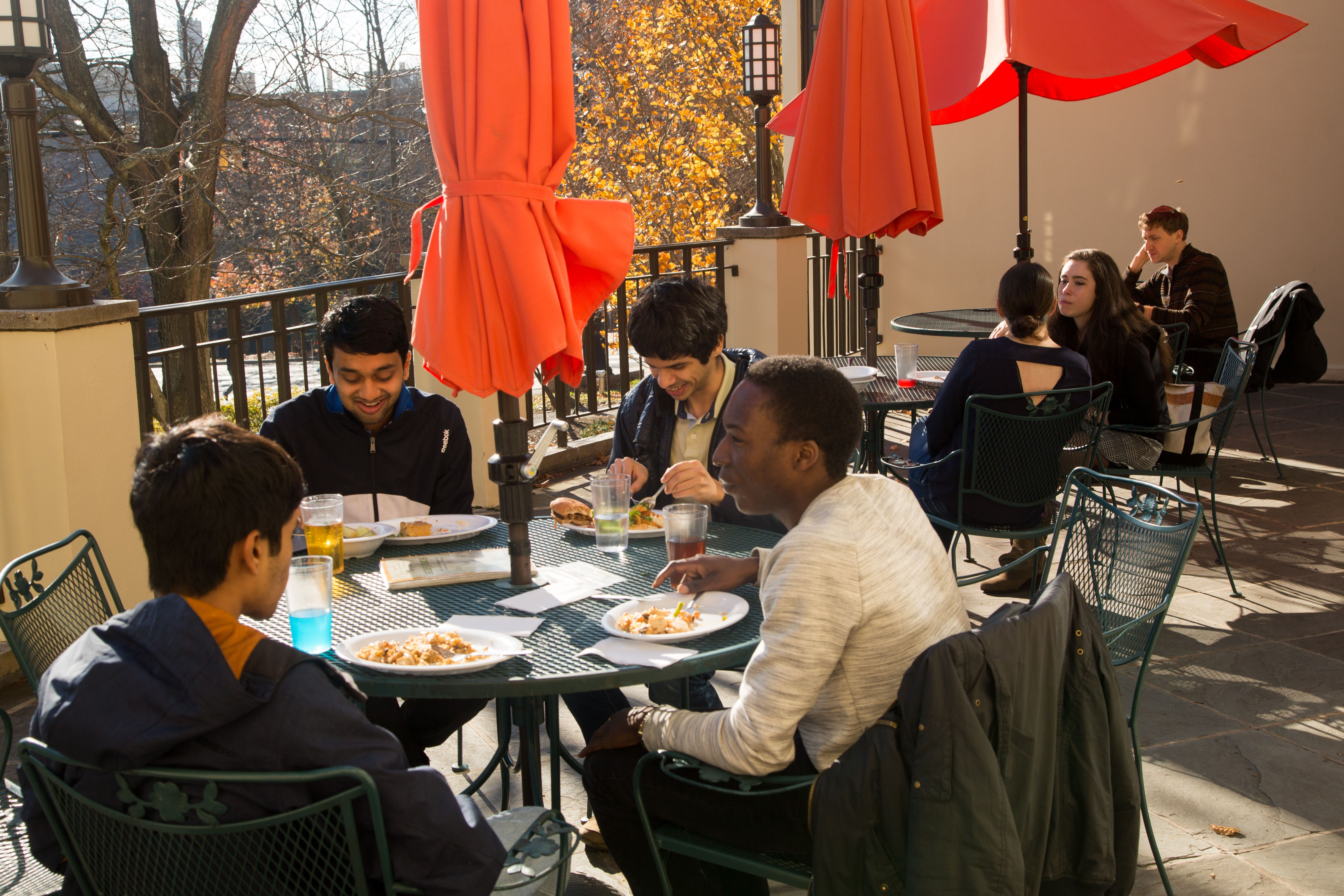 Students eating outside on a terrace.