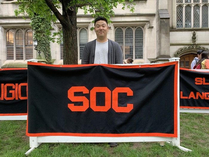 Daniel standing behind the Sociology concentration banner