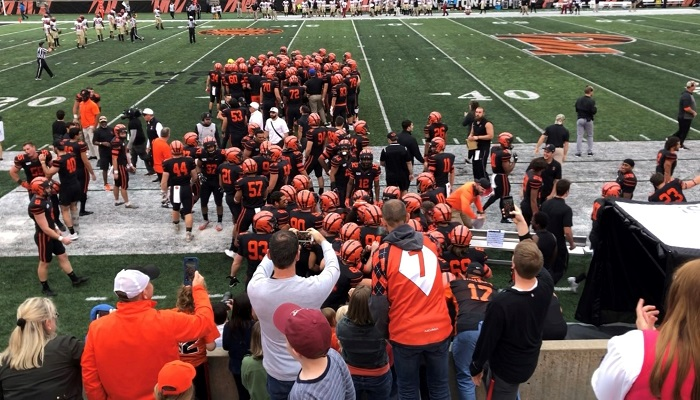 Princeton football players in a huddle on the football field during a game