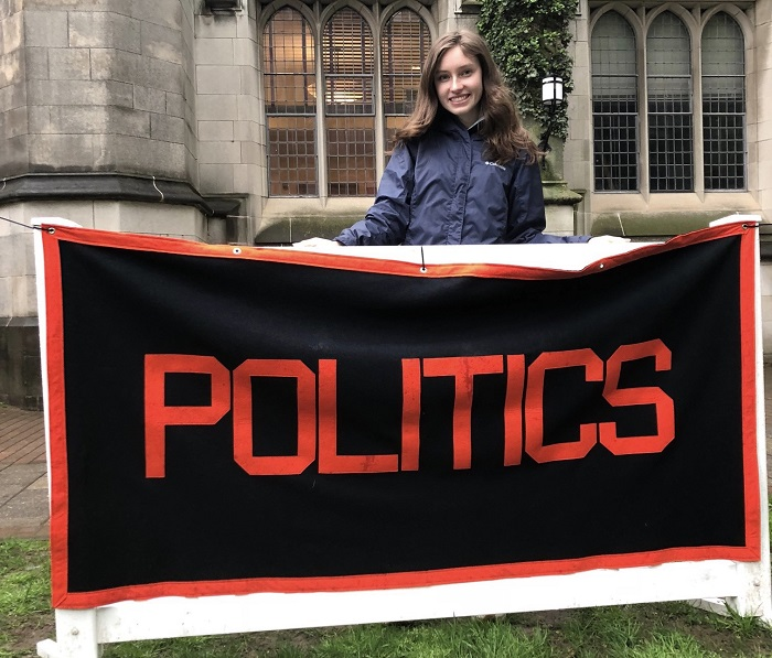Mallory standing behind the Politics concentration banner