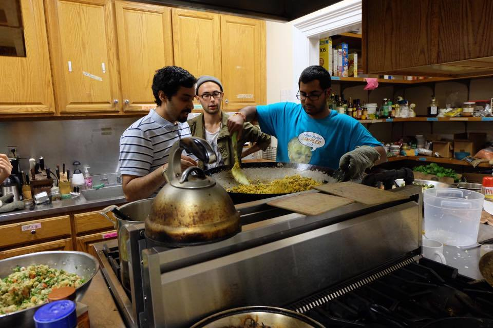 Three students cooking rice in a wok
