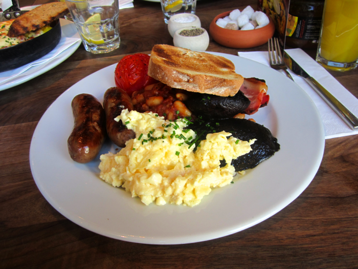 A picture of a typical English Breakfast: eggs, bacon, beans, mushrooms, tomatoes, sausages, and toast.