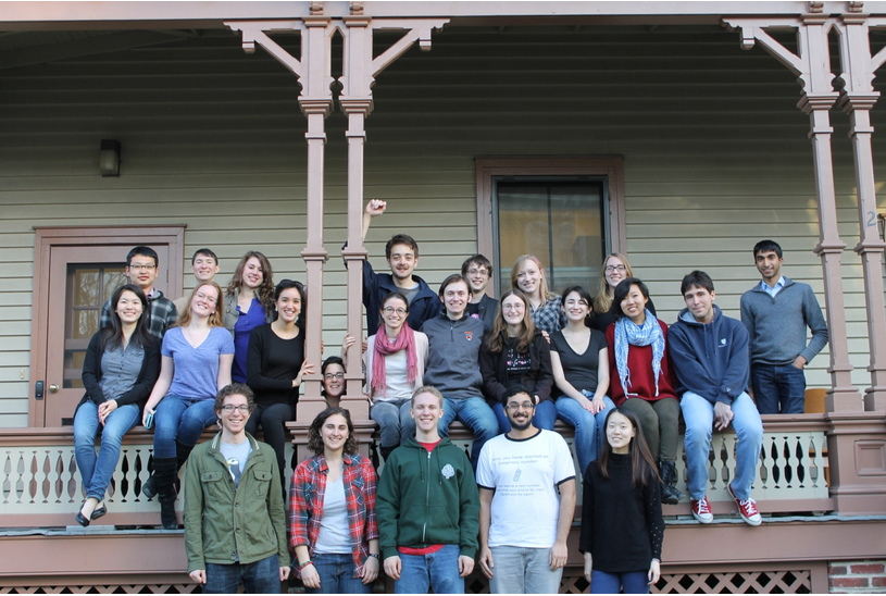 Many students in front of a wooden house