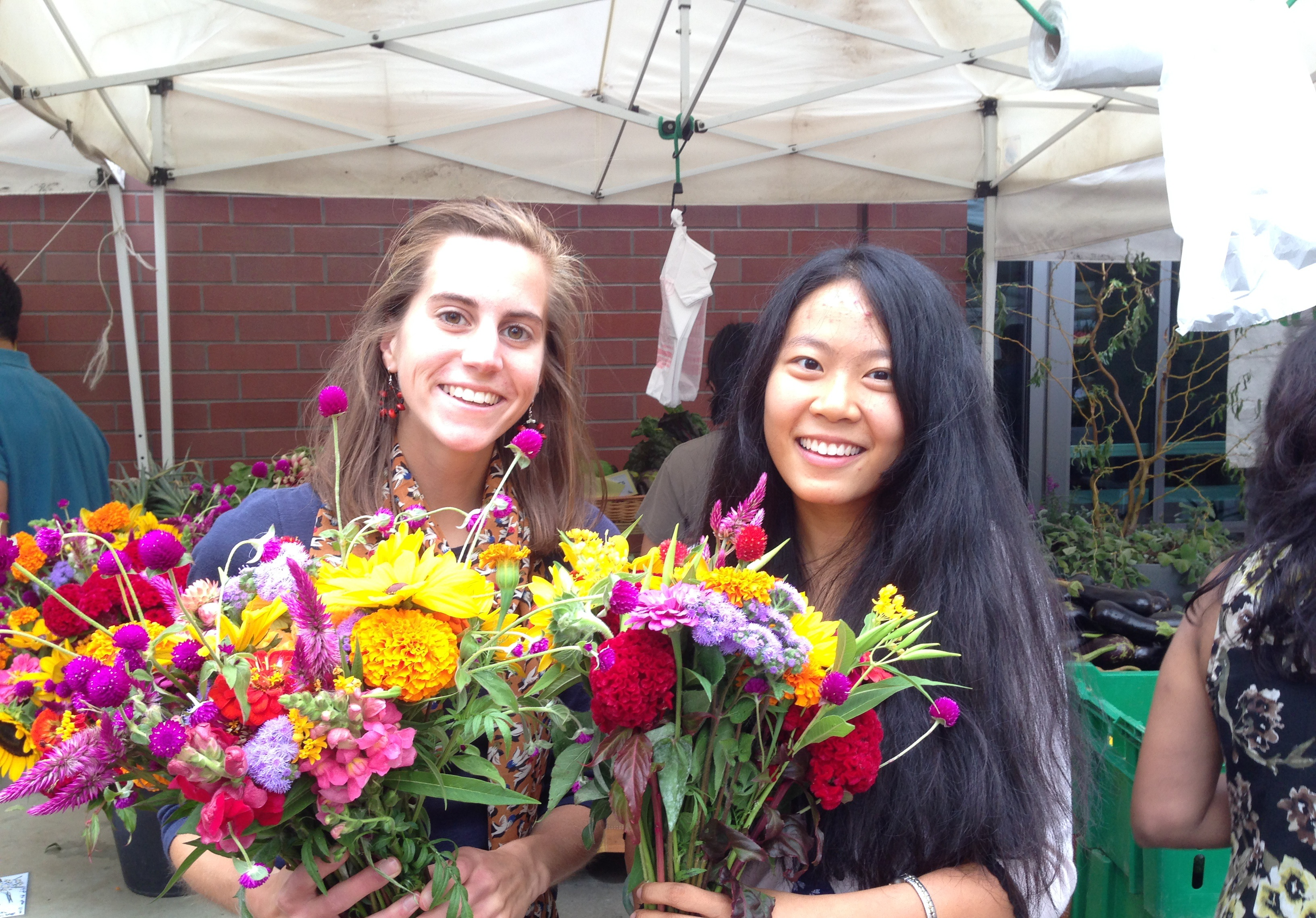 This is a photo of my friend and me with flowers from the farmer's market.