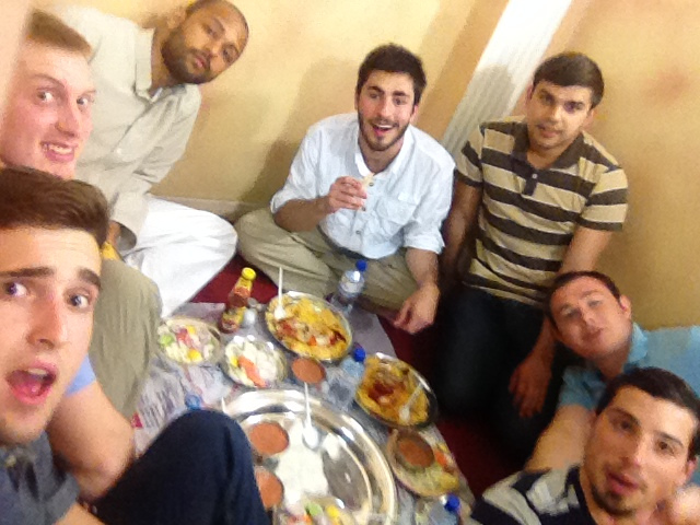 Several young men, including yours truly, crowded around a plate in a very cramped dining area.