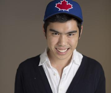 Kevin Wong standing, smiling and wearing baseball cap