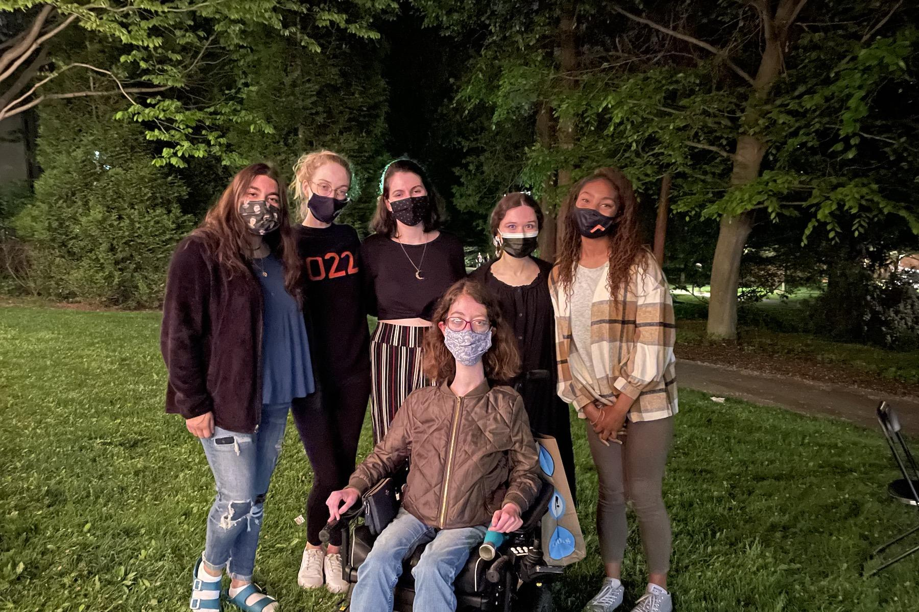Naomi surrounded by five friends, all wearing masks