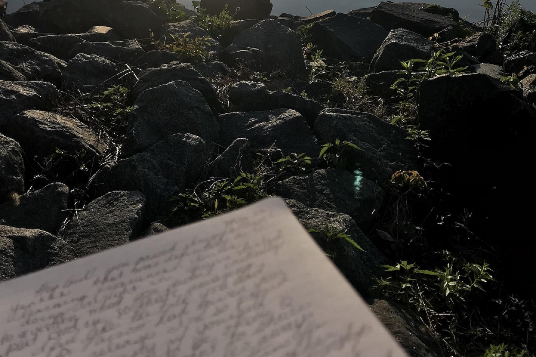 Notebook with script writing against a backdrop of rocks by the water