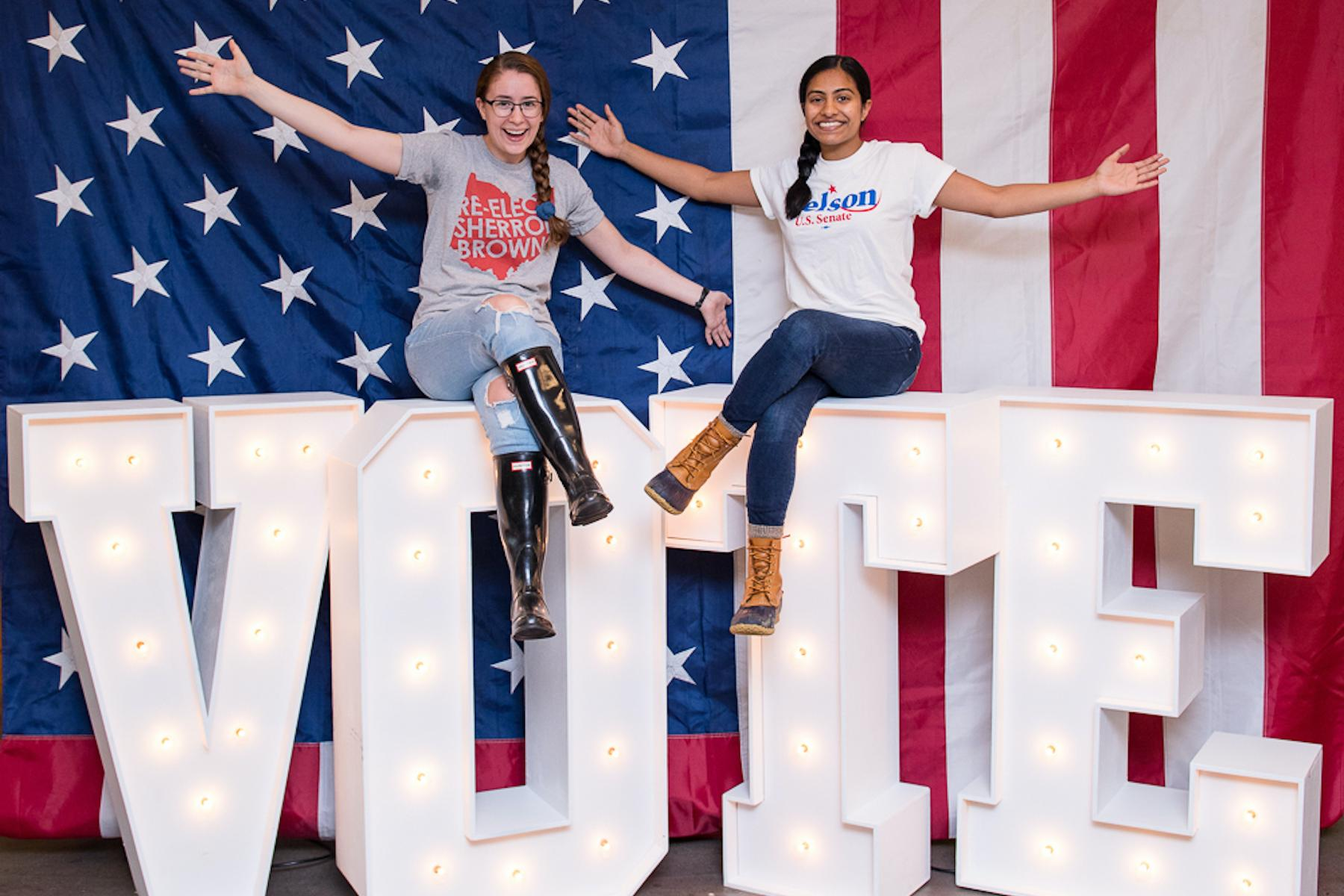 Two female students sitting atop giant white letters that say vote with an American flag backdrop