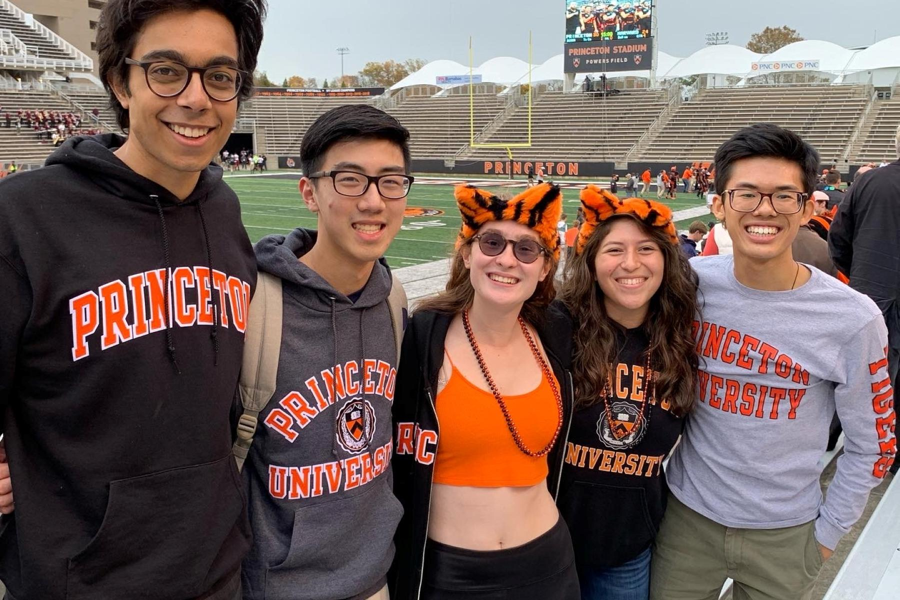 A group of friends celebrating a Princeton victory at the football stadium.