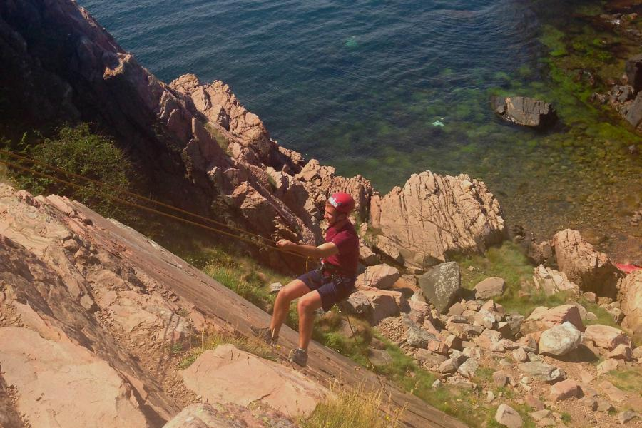 Repelling down a cliff on Kullaberg Peninsula