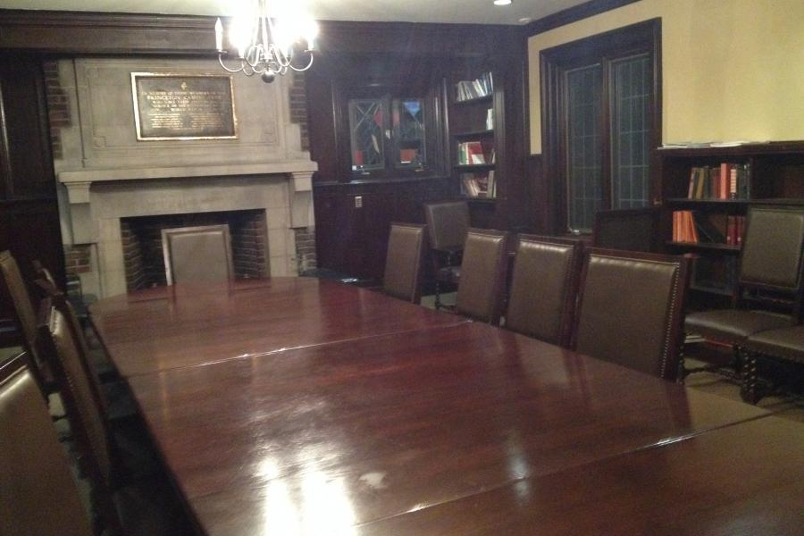 A room with a  long, shiny table and a stone fireplace on the far side.
