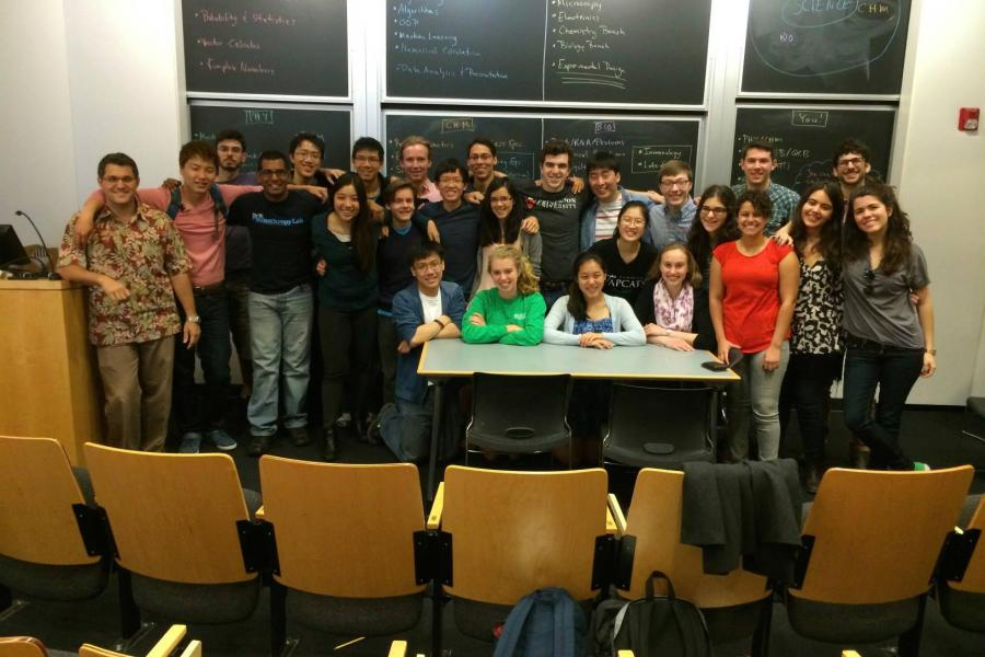 Students and teachers in front of a blackboard