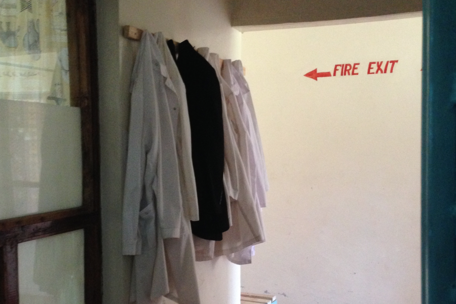 White coats hanging in a hallway.