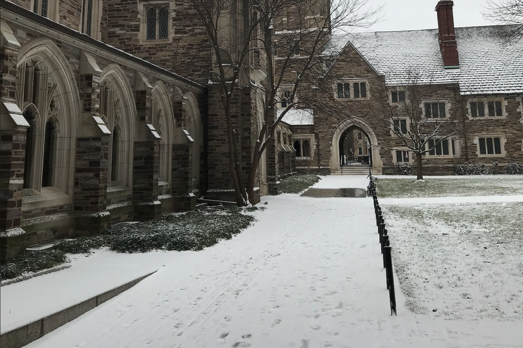 Mathey College courtyard with an inch of snow on the ground. There are footprints visible in the snow along the walkways.