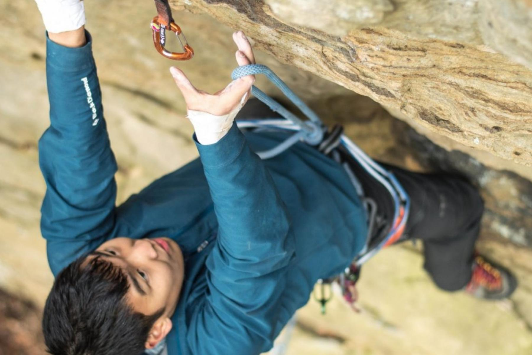 A Princeton student reaches to attach his rope at the Outdoor Action climbing gym