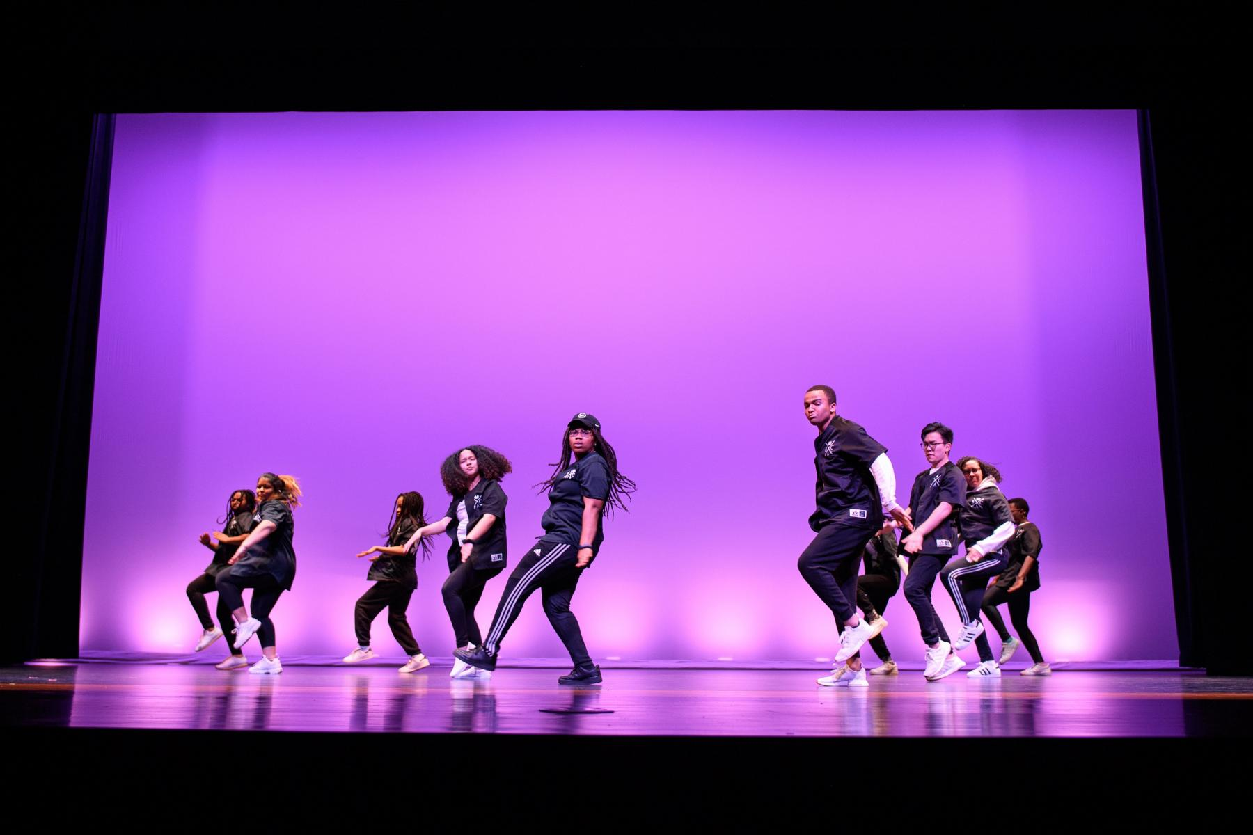 Student group performing a dance on stage