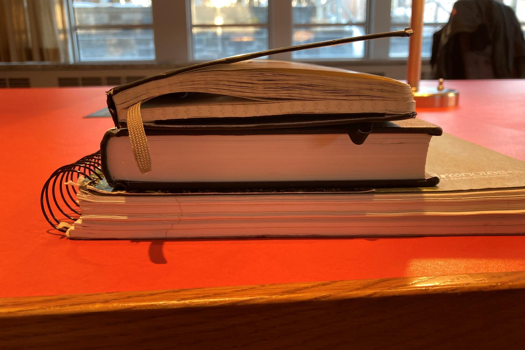 A stack of a large spiral notebook, a black hardcover textbook and a black moleskin notebook on an orange desk at Firestone. In the background, large windows can be seen.