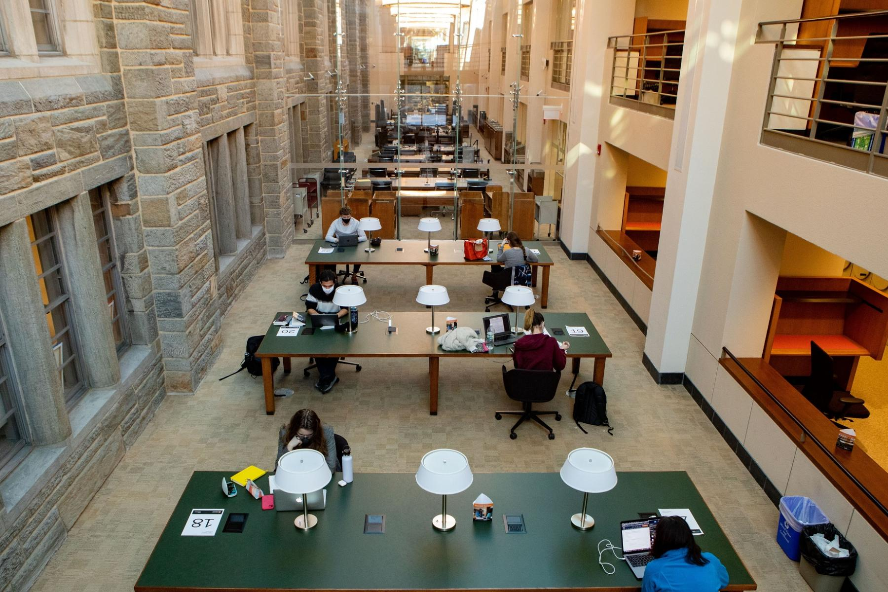 Masked students studying in library