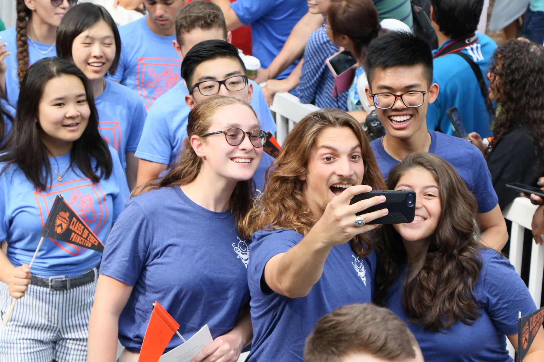 First-year students taking a sefie as they walk the Pre-rade