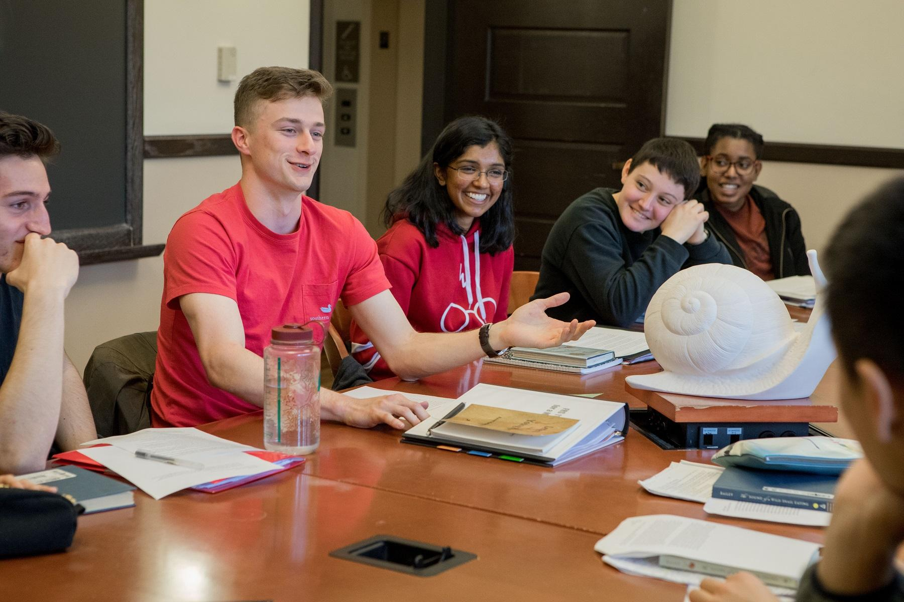 Student in a small discussion class surrounded by four students.
