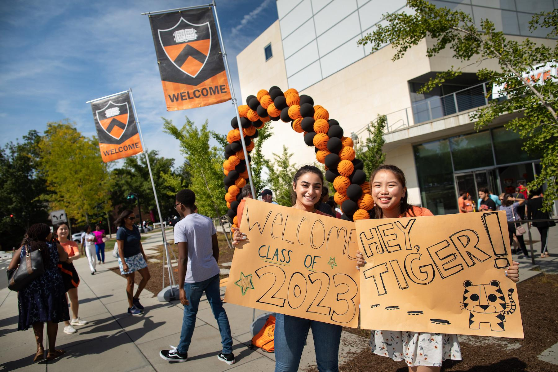"Two students holding posters that say ""Welcome, Class of 2023"" and ""Hey, Tiger!"""