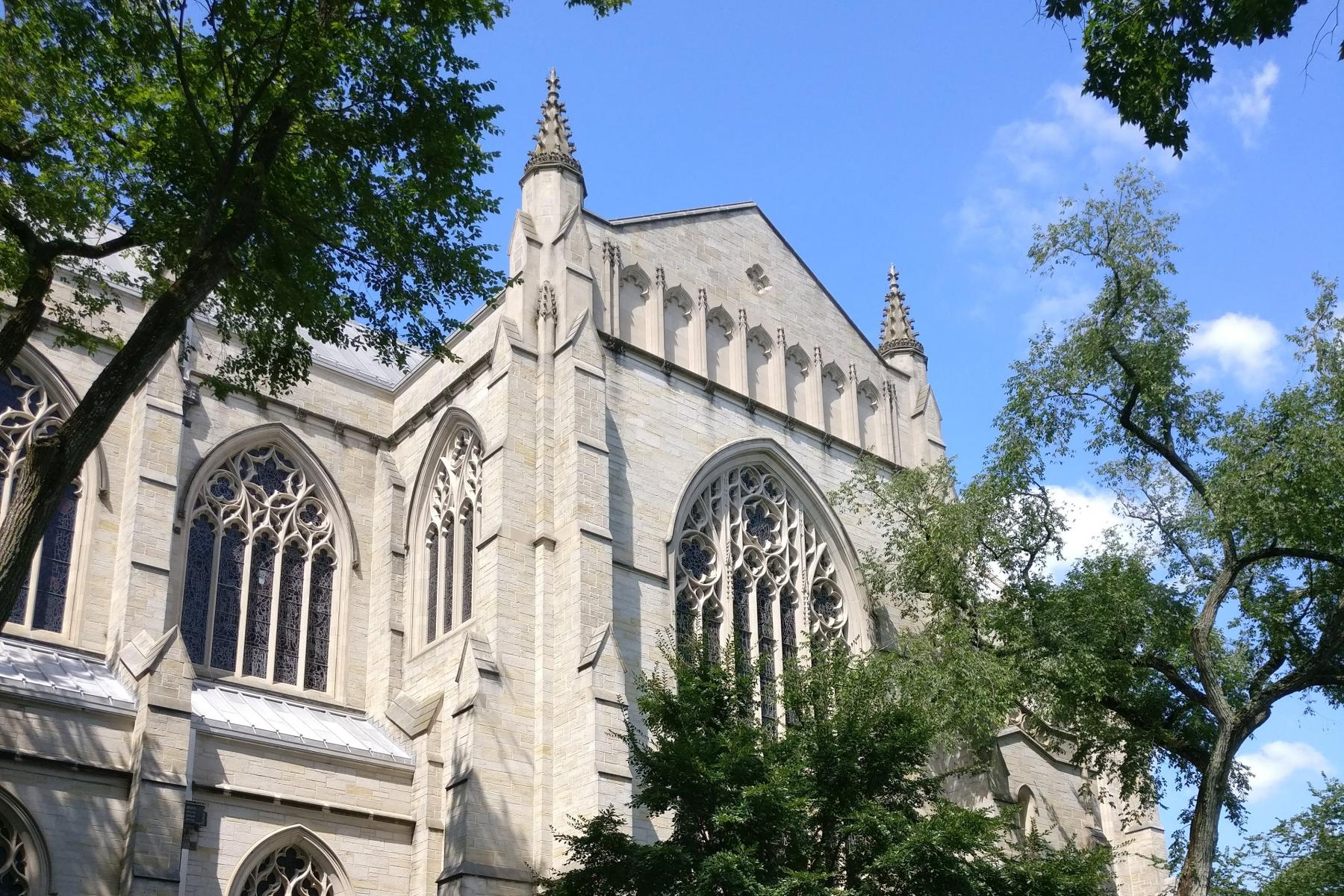 A photo of the side of the Chapel on a sunny day, framed by trees.