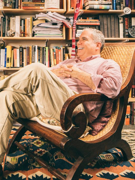 Miguel Centeno sitting in a rocking chair looking off, smiling