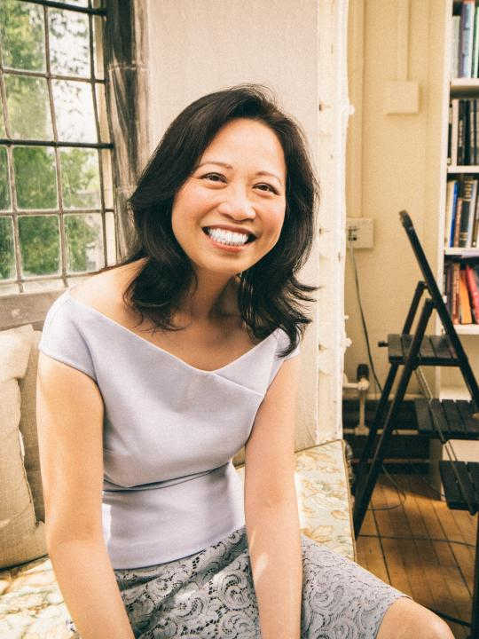 Anne Cheng sitting on couch, smiling at camera