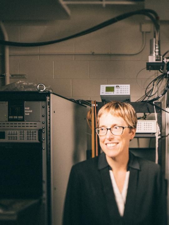 Suzanne Staggs standing in lab looking off-camera smiling
