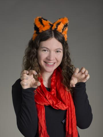 Michelle Greenfield posing like a tiger wearing plush tiger ears