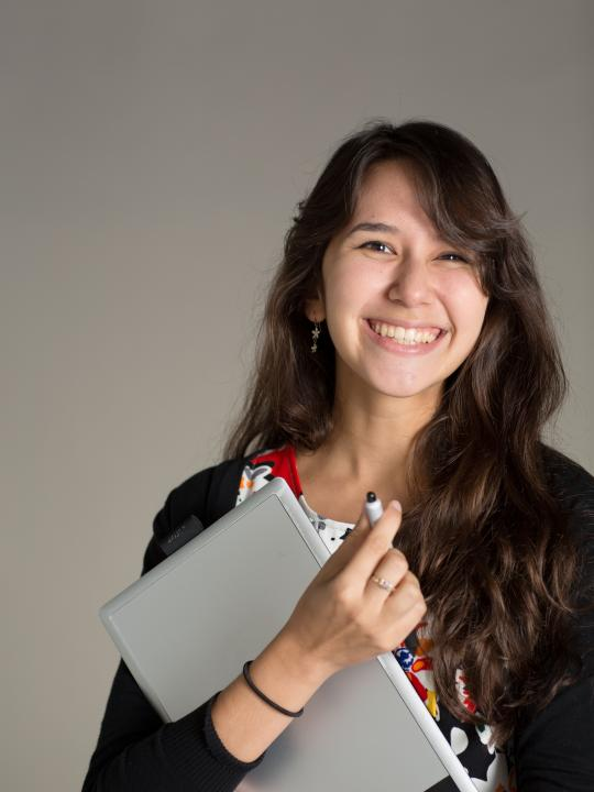 Aliisa Lee smiling holding a laptop