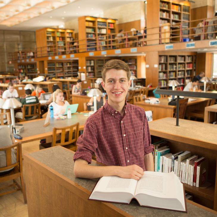 Newby Parton standing in library with book