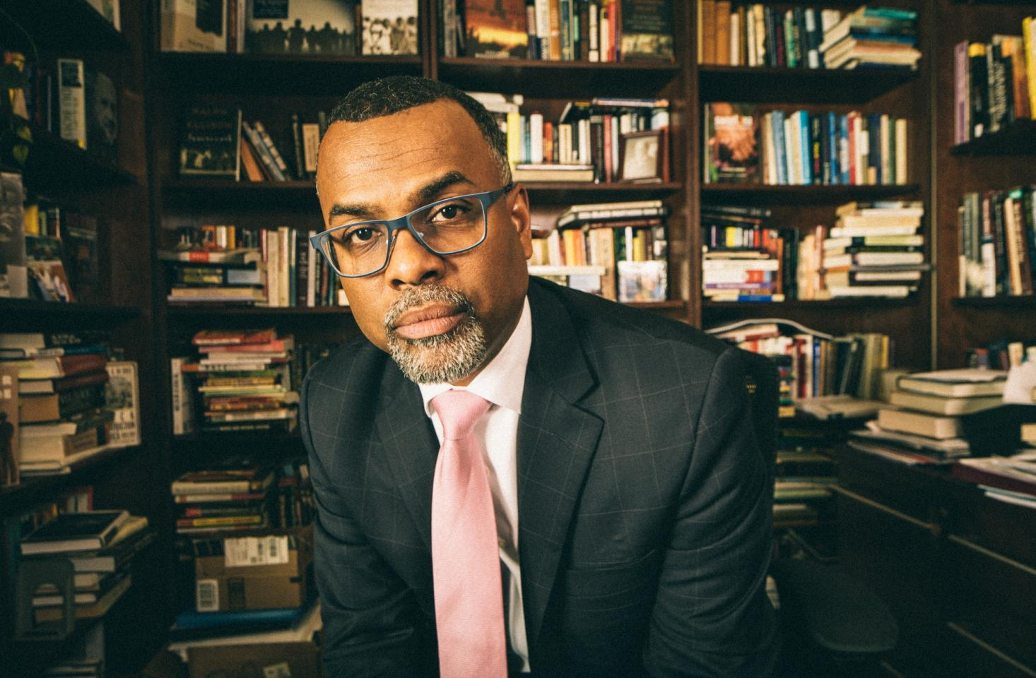 Eddie Glaude sitting in front of bookcases looking at camera