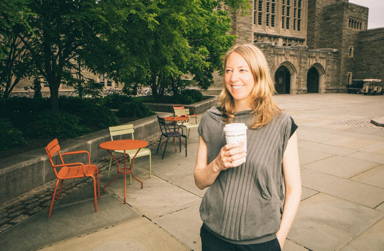Brooke Holmes standing in courtyard holding coffee cup smiling